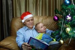 Χριστουγεννιάτικο δέντρο, παππούς και εγγονός στοκ εικόνα