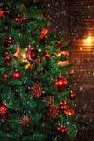 Χριστουγεννιάτικο δέντρο που διακοσμείται με την κόκκινη κινηματογράφηση σε πρώτο πλάνο γιρλαντών κώνων πεύκων διακοσμήσεων στοκ φωτογραφίες με δικαίωμα ελεύθερης χρήσης