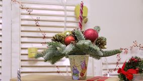 Χριστουγεννιάτικο δέντρο στο γυαλί, που διακοσμείται με τις πολύχρωμους σφαίρες, τους κώνους και τα κεριά φιλμ μικρού μήκους