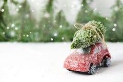 Χριστουγεννιάτικο δέντρο στο κόκκινο παιχνίδι αυτοκινήτων με το χιόνι Έννοια χειμερινών διακοπών Στοκ Εικόνες