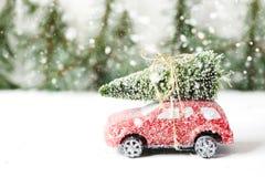 Χριστουγεννιάτικο δέντρο στο κόκκινο παιχνίδι αυτοκινήτων με το χιόνι Έννοια χειμερινών διακοπών Στοκ εικόνα με δικαίωμα ελεύθερης χρήσης