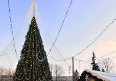 Χριστουγεννιάτικο δέντρο τη διακόσμηση που εγκαθίσταται με σε Vilnius στο ηλιοβασίλεμα Στοκ Φωτογραφία