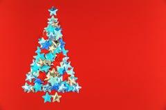 Χριστουγεννιάτικο δέντρο των αστεριών στο κόκκινο υπόβαθρο στοκ φωτογραφίες