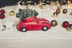 χριστουγεννιάτικο δώρο κόκκινο παιχνίδι αυτοκινήτων με το χριστουγεννιάτικο δέντρο στην κορυφή στο whi Στοκ Φωτογραφίες
