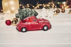 χριστουγεννιάτικο δώρο κόκκινο παιχνίδι αυτοκινήτων με το χριστουγεννιάτικο δέντρο στην κορυφή στο whi Στοκ εικόνα με δικαίωμα ελεύθερης χρήσης