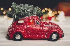 χριστουγεννιάτικο δώρο κόκκινο παιχνίδι αυτοκινήτων με το χριστουγεννιάτικο δέντρο στην κορυφή στο whi Στοκ εικόνες με δικαίωμα ελεύθερης χρήσης