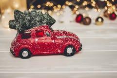 χριστουγεννιάτικο δώρο κόκκινο παιχνίδι αυτοκινήτων με το χριστουγεννιάτικο δέντρο στην κορυφή στο whi Στοκ φωτογραφίες με δικαίωμα ελεύθερης χρήσης