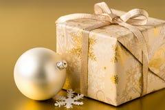 Χριστουγεννιάτικο δώρο και μπιχλιμπίδι στο χρυσό υπόβαθρο Στοκ Φωτογραφίες
