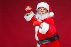 Χριστούγεννα Άγιος Βασίλης με την κόκκινη πληγή επιδέσμων σε ετοιμότητα του για τον εγκιβωτισμό μιμείται τα λακτίσματα Kickboxing στοκ φωτογραφίες με δικαίωμα ελεύθερης χρήσης