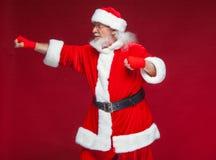 Χριστούγεννα Άγιος Βασίλης με την κόκκινη πληγή επιδέσμων σε ετοιμότητα του για τον εγκιβωτισμό μιμείται τα λακτίσματα Kickboxing στοκ φωτογραφίες