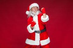 Χριστούγεννα Άγιος Βασίλης με την κόκκινη πληγή επιδέσμων σε ετοιμότητα του για τον εγκιβωτισμό μιμείται τα λακτίσματα Kickboxing στοκ εικόνα