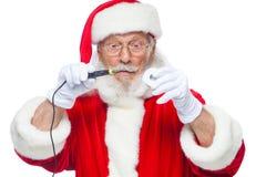 Χριστούγεννα Άγιος Βασίλης στα άσπρα γάντια που κρατά έναν συγκολλώντας σίδηρο με μια ύλη συγκολλήσεως Ηλεκτρονική, επισκευή εξοπ στοκ φωτογραφίες