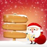 Χριστούγεννα Άγιος Βασίλης readind ένας χάρτης με τον ξύλινο κενό πίνακα σημαδιών Στοκ Εικόνα