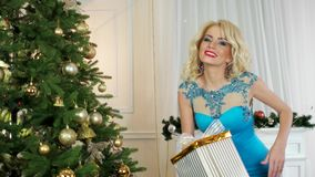 Χριστούγεννα, έκπληξη του νέου έτους, πορτρέτο ενός κοριτσιού που δίνει ένα δώρο, στο υπόβαθρο ο εορτασμός των Χριστουγέννων απόθεμα βίντεο
