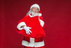 Χριστούγεννα Ένας καλός χαμογελώντας Άγιος Βασίλης κρατά ότι μια κόκκινη τσάντα με παρουσιάζει μπροστά από τον που αγκαλιάζει το  στοκ εικόνες
