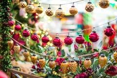 Χριστούγεννα ένωσης και νέες διακοσμήσεις έτους - κόκκινες και χρυσές σφαίρες στο θολωμένο υπόβαθρο αγοράς Μαλακή εκλεκτική εστία στοκ φωτογραφία με δικαίωμα ελεύθερης χρήσης