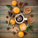 Χριστούγεννα ή νέα έννοια έτους με τους κώνους πεύκων, την κούπα καφέ, το μανταρίνι και την κανέλα στο ξύλινο υπόβαθρο Επίπεδος β Στοκ Φωτογραφία