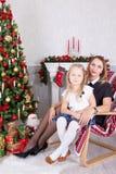 Χριστούγεννα ή νέος εορτασμός έτους Ευτυχής συνεδρίαση μητέρων και κορών στην καρέκλα κοντά στο χριστουγεννιάτικο δέντρο με τα δώ Στοκ φωτογραφίες με δικαίωμα ελεύθερης χρήσης