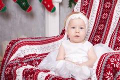 Χριστούγεννα ή νέος εορτασμός έτους Λίγο χαριτωμένο κορίτσι στο άσπρο εορταστικό φόρεμα κάθεται σε μια καρέκλα με το καρό με τη δ Στοκ Εικόνες
