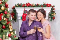 Χριστούγεννα ή νέος εορτασμός έτους Νέο όμορφο ζεύγος με ένα γυαλί της συνεδρίασης σαμπάνιας κοντά στο χριστουγεννιάτικο δέντρο μ Στοκ Εικόνες