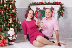 Χριστούγεννα ή νέος εορτασμός έτους Νέο όμορφο ζεύγος με ένα γυαλί της συνεδρίασης σαμπάνιας κοντά στο χριστουγεννιάτικο δέντρο μ Στοκ φωτογραφία με δικαίωμα ελεύθερης χρήσης