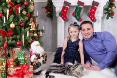Χριστούγεννα ή νέος εορτασμός έτους Παιχνίδι πατέρων και κορών με τη γάτα κοντά στο χριστουγεννιάτικο δέντρο happy holidays Στοκ εικόνα με δικαίωμα ελεύθερης χρήσης