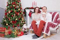Χριστούγεννα ή νέος εορτασμός έτους Πορτρέτο της εύθυμης νέας οικογένειας τριών ανθρώπων κοντά στο χριστουγεννιάτικο δέντρο με τα Στοκ φωτογραφίες με δικαίωμα ελεύθερης χρήσης