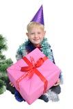 Χριστούγεννα αγοριών κοντά στο νέο παρόν έτος δέντρων στοκ εικόνες