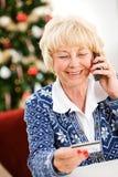 Χριστούγεννα: Γυναίκα που χρησιμοποιεί την πιστωτική κάρτα πέρα από το τηλέφωνο Στοκ Εικόνες