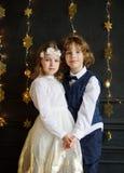 Χριστούγεννα Δύο festively ντυμένα παιδιά, αγόρι και κορίτσι, κρατούν τα χέρια Στοκ Φωτογραφία