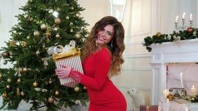 Χριστούγεννα εορτασμού, κορίτσι με το δώρο ενός νέου έτους υπό εξέταση, ενάντια στο σκηνικό των ερυθρελατών που διακοσμούνται με  απόθεμα βίντεο