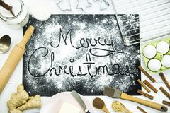 Χριστούγεννα εύθυμα γραπτός σε έναν μαύρο πίνακα που ψεκάζεται με το αλεύρι Έννοια μαγειρέματος Χριστουγέννων Στοκ φωτογραφία με δικαίωμα ελεύθερης χρήσης