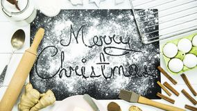 Χριστούγεννα εύθυμα γραπτός σε έναν μαύρο πίνακα που ψεκάζεται με το αλεύρι Έννοια μαγειρέματος Χριστουγέννων Στοκ εικόνα με δικαίωμα ελεύθερης χρήσης