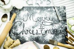 Χριστούγεννα εύθυμα γραπτός σε έναν μαύρο πίνακα που ψεκάζεται με το αλεύρι Έννοια μαγειρέματος Χριστουγέννων Στοκ Εικόνες