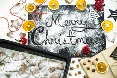 Χριστούγεννα εύθυμα γραπτός σε έναν μαύρο πίνακα που ψεκάζεται με το αλεύρι Έννοια μαγειρέματος Χριστουγέννων Στοκ Φωτογραφία