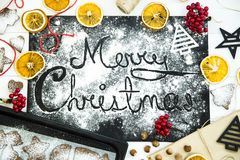 Χριστούγεννα εύθυμα γραπτός σε έναν μαύρο πίνακα που ψεκάζεται με το αλεύρι Έννοια μαγειρέματος Χριστουγέννων Στοκ Φωτογραφίες