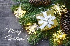 Χριστούγεννα εύθυμα Κιβώτιο δώρων Χριστουγέννων, κώνοι πεύκων και snowflakes στο παλαιό ξύλινο υπόβαθρο Έννοια χειμερινών διακοπώ Στοκ Φωτογραφίες