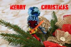 Χριστούγεννα εύθυμα Κομψός κλάδος με τις διακοσμήσεις και την κούκλα Η Χαρούμενα Χριστούγεννα επιγραφής Στοκ Φωτογραφίες