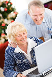 Χριστούγεννα: Ζεύγος που γελά στο αστείο ηλεκτρονικό ταχυδρομείο Στοκ Φωτογραφίες