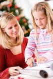 Χριστούγεννα: Η μητέρα βοηθά το κορίτσι να κόψει το κομμάτι από το ρόλο τυλίγοντας εγγράφου Στοκ Φωτογραφία