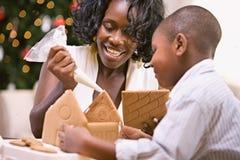Χριστούγεννα: Η μητέρα και ο γιος χτίζουν το σπίτι μελοψωμάτων διακοπών Στοκ Εικόνες