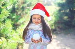 Χριστούγεννα και έννοια ανθρώπων - λίγο παιδί στο καπέλο santa με τη χιονιά Στοκ εικόνες με δικαίωμα ελεύθερης χρήσης