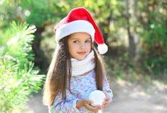 Χριστούγεννα και έννοια ανθρώπων - πορτρέτο λίγο παιδί στο καπέλο santa με τη χιονιά Στοκ φωτογραφία με δικαίωμα ελεύθερης χρήσης