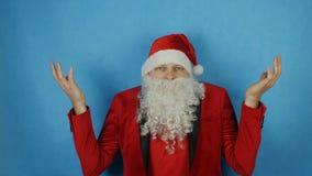 Χριστούγεννα και νέο έτος, άτομο όπως έναν Άγιο Βασίλη που εκπλήσσεται και που συγκλονίζεται, στο μπλε υπόβαθρο απόθεμα βίντεο