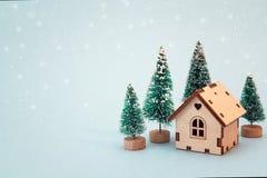 Χριστούγεννα και νέο μικροσκοπικό σπίτι έτους με τα δέντρα έλατου στο μπλε β Στοκ Εικόνα