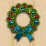Χριστούγεννα και νέο στεφάνι έτους Πράσινος κλάδος του έλατου με τις κόκκινες, μπλε σφαίρες και του μπλε τόξου στο ξύλινο υπόβαθρ Στοκ εικόνα με δικαίωμα ελεύθερης χρήσης