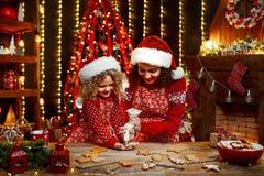 Χριστούγεννα καλές διακ& Εύθυμο χαριτωμένο σγουρό μικρό κορίτσι και η παλαιότερη αδελφή της στο μαγείρεμα καπέλων santas στοκ φωτογραφία