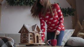Χριστούγεννα καλές διακ& Η νέα γυναίκα πίνει το θερμό τσάι με τα μπισκότα Χριστουγέννων απόθεμα βίντεο