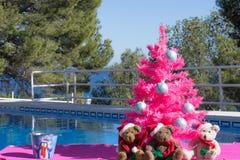 Χριστούγεννα καλές διακ& Τρία Santa αντέχουν και ένα ρόδινο χριστουγεννιάτικο δέντρο από την πισίνα στοκ φωτογραφίες