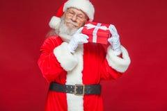 Χριστούγεννα Καλός Άγιος Βασίλης στα άσπρα γάντια κρατά ένα κόκκινο κιβώτιο δώρων με ένα τόξο κοντά σε ένα αυτί Ακούει Απομονωμέν στοκ φωτογραφία με δικαίωμα ελεύθερης χρήσης